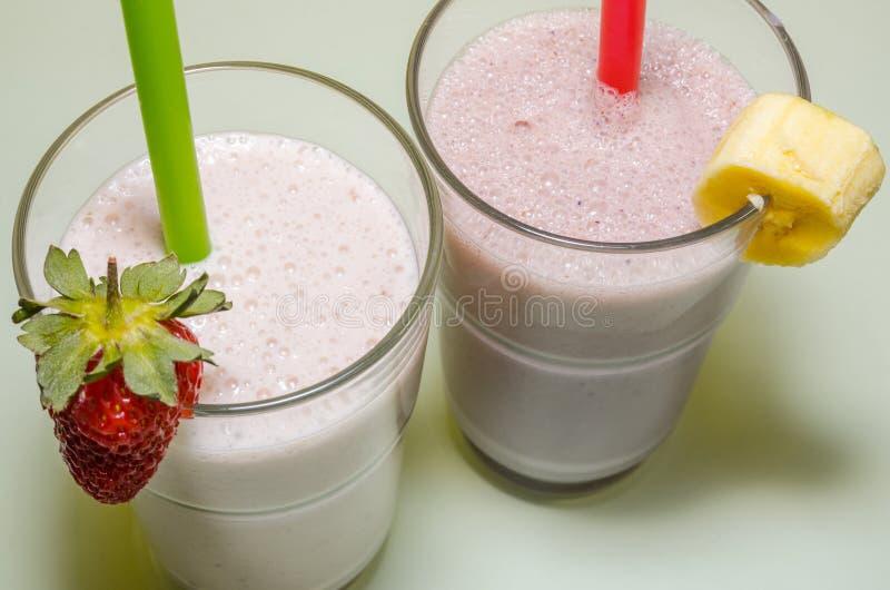 Zwei Milchshaken mit Banane und Erdbeere stockfoto