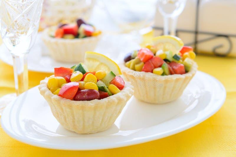 Zwei Minitörtchen mit Salat vom Zuckermais, von den Gartenbohnen und vom Avocadosalat auf festlicher Tabelle lizenzfreies stockbild