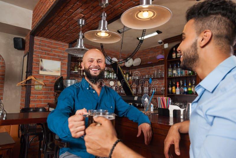 Zwei Mischungs-Rennmann in den Bar-Geklirr-Gläsern röstend, trinkende Bier-Griff-Becher, nettes Freund-Treffen stockbild