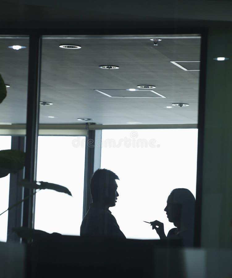 Zwei Mitarbeiter, die im Büro, Schattenbild sprechen stockbilder
