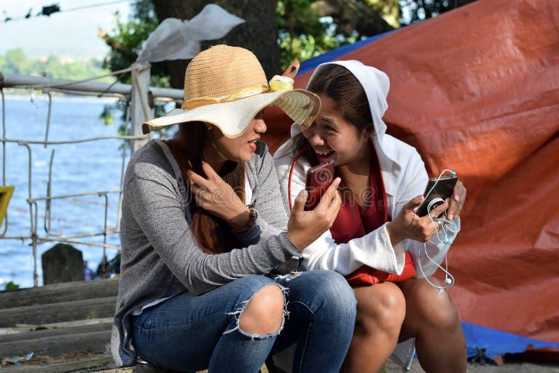Zwei 2 Mittegreisinnen, welche den Spaß teilt die Gedanken und Geschichten halten intelligentes Telefon haben stockfotos