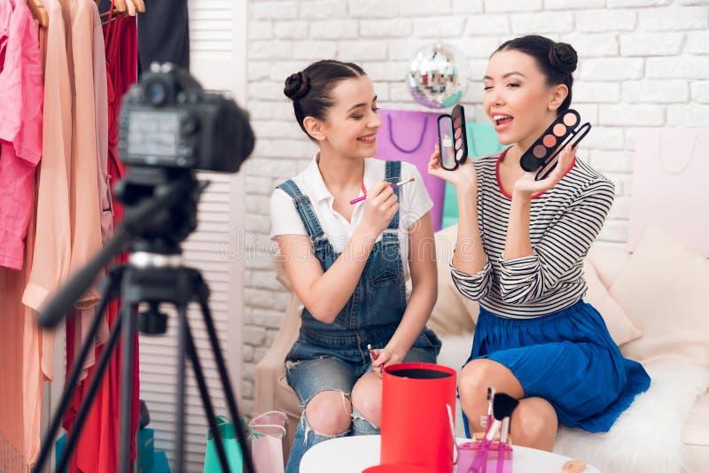 Zwei Mode Bloggermädchen halten Bürsten und Lidschatten zur Kamera lizenzfreies stockbild
