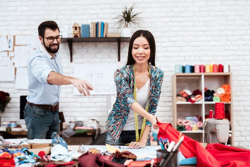 Zwei Modedesigner, die über rotem Stoff hanfing sind stockbilder