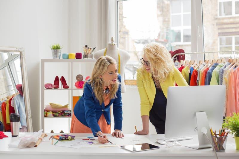 Zwei Modedesigner, die etwas besprechen stockbild