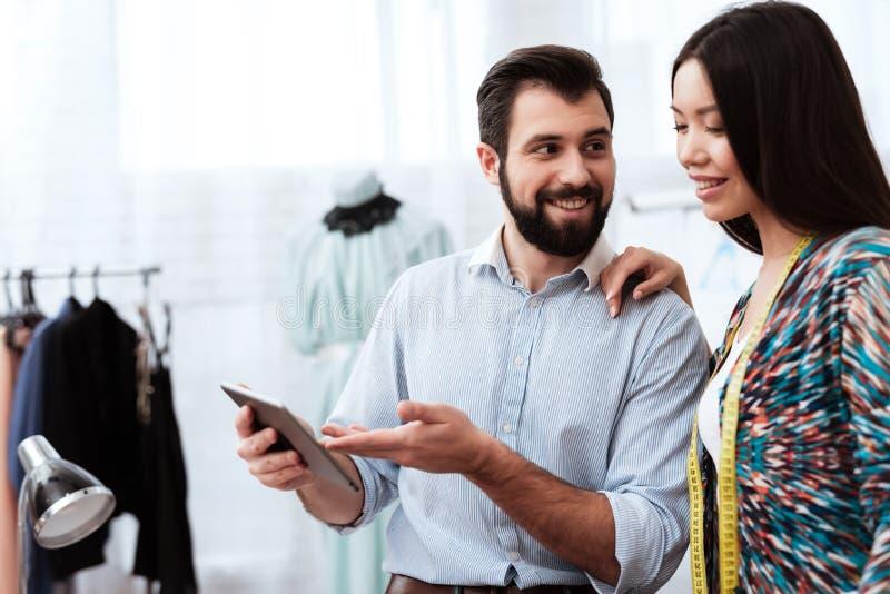 Zwei Modedesigner, die Tablette betrachten lizenzfreie stockbilder