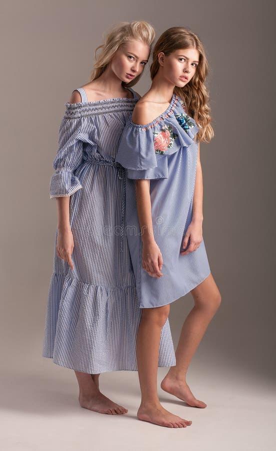 Zwei Modelle in den blauen Kleidern, die auf grauem Hintergrund aufwerfen lizenzfreies stockfoto