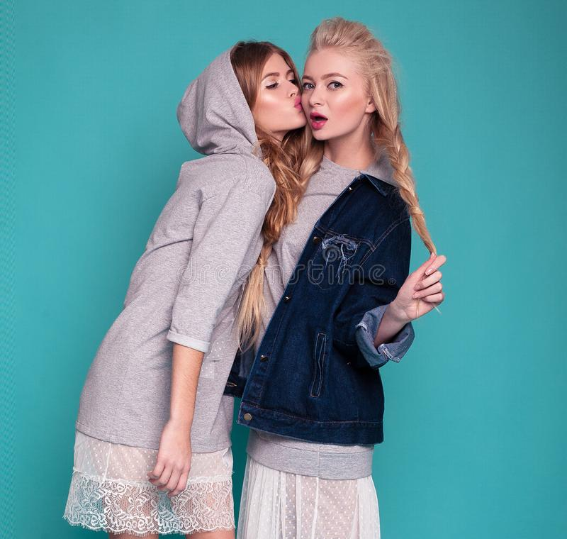 Zwei Modelle in den Kleidern und in Jacken, die auf blauem Hintergrund aufwerfen lizenzfreies stockfoto