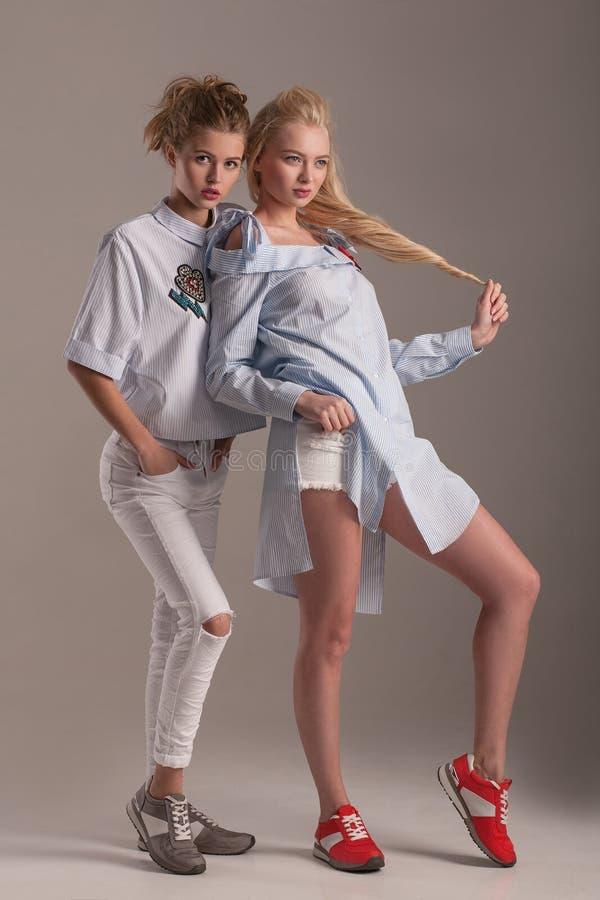 Zwei Modelle im Kleid, Bluse, Jeans und kichert die Schuhe, die herein aufwerfen lizenzfreie stockfotos