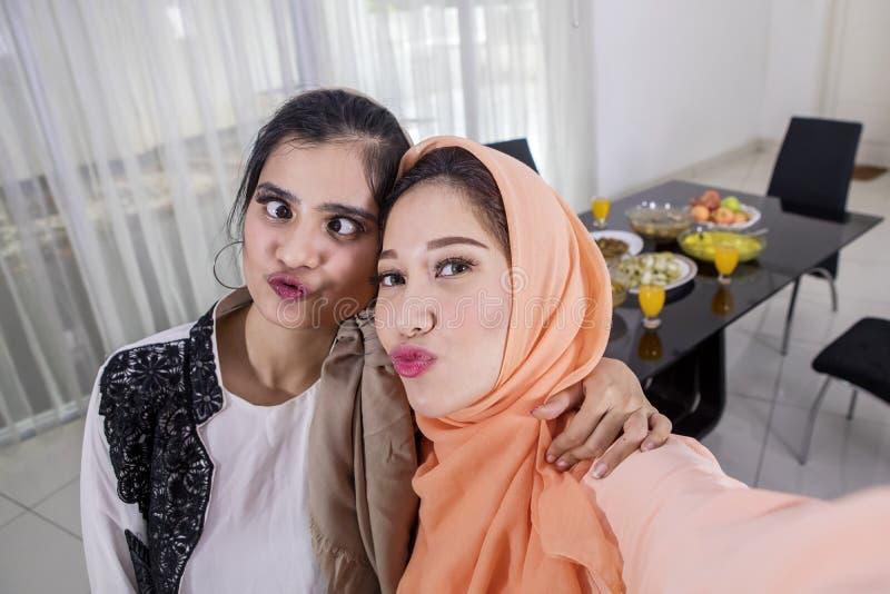 Zwei moslemische Frauen machen Fotos mit Entengesicht stockbilder