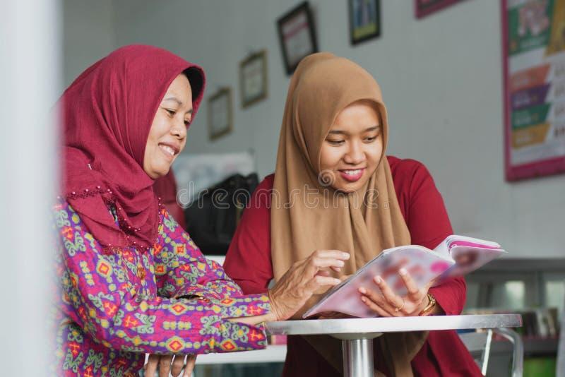 Zwei moslemische Hijab Frau, die eine Zeitschrift sitzt innerhalb ihres Modespeichers liest lizenzfreie stockfotos
