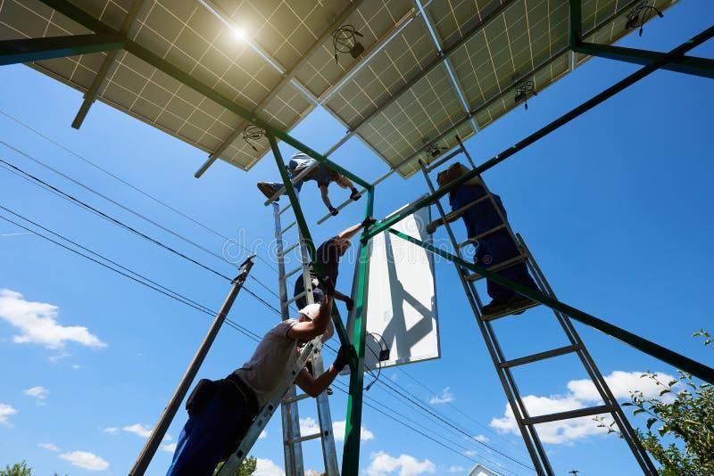 Zwei mounters, die Solarbatterien auf metallische Karkasse installieren lizenzfreie stockfotografie