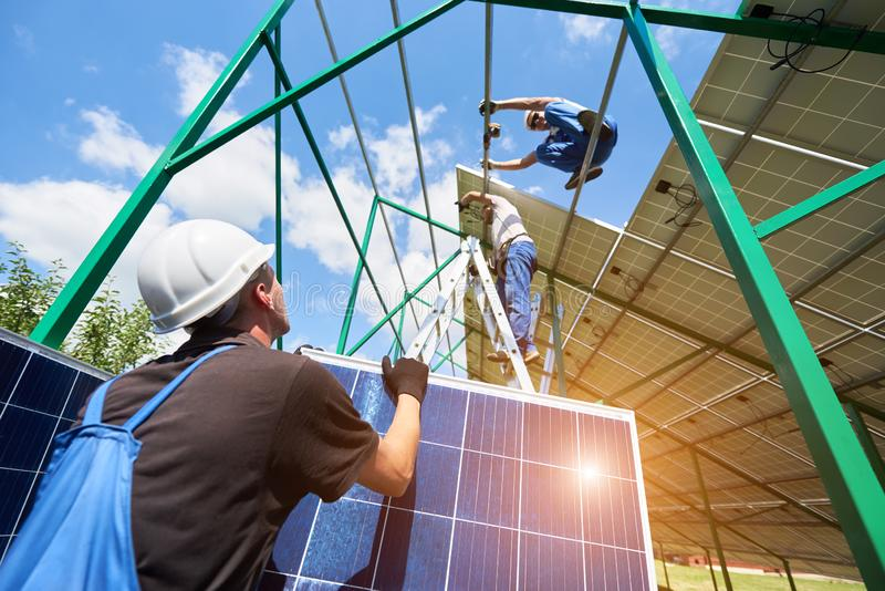 Zwei mounters, die Solarbatterien auf metallischen Bau installieren lizenzfreies stockfoto