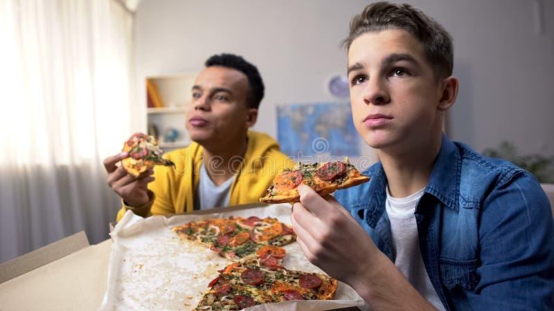 Zwei multiethnische männliche Teenager essen Pizza und schauen sich TV-Show an, Freizeit stockfotografie