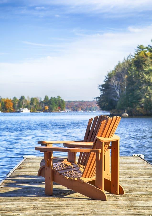 Zwei Muskoka-Stühle auf einem hölzernen Dock an einem blauen See lizenzfreies stockbild