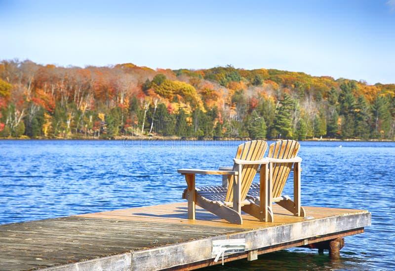 Zwei Muskoka-Stühle auf einem hölzernen Dock an einem blauen See lizenzfreie stockfotografie