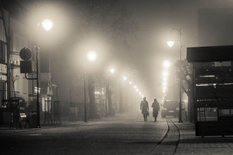 Zwei mysteriöse Leute gehen entlang eine nebelige Straße angesichts der Nachtlampen stockfoto