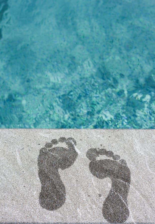 Zwei nasse Fußjobsteps durch Swimmingpool stockfotos