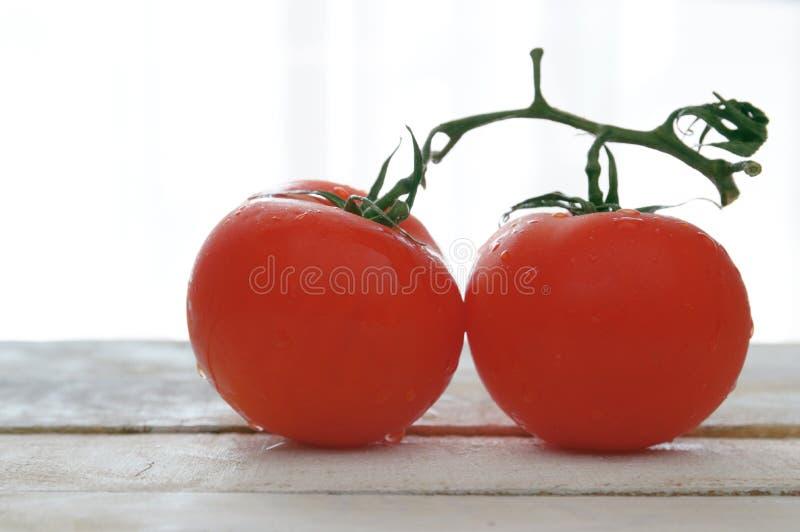 Zwei natürliche Tomaten auf einem weißen Holztisch stockbilder