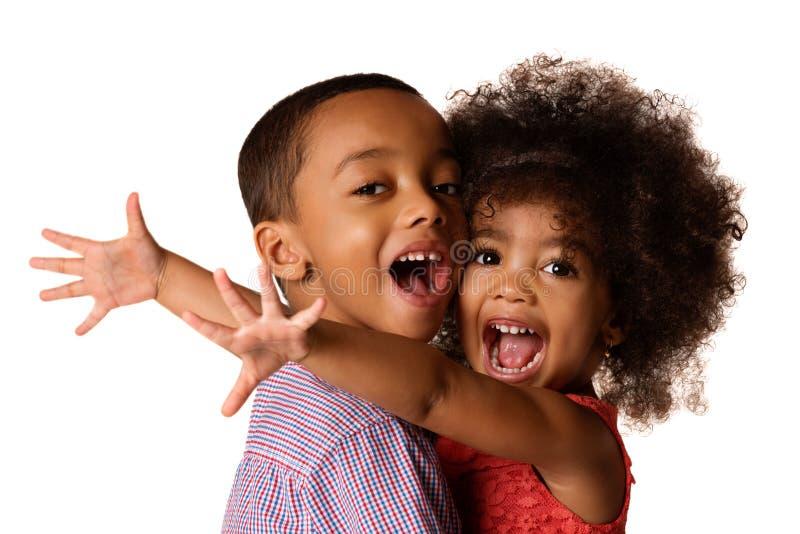 Zwei nette Afroamerikanergeschwister, Schwester, die ihren Bruder, lokalisiert umarmt lizenzfreies stockbild