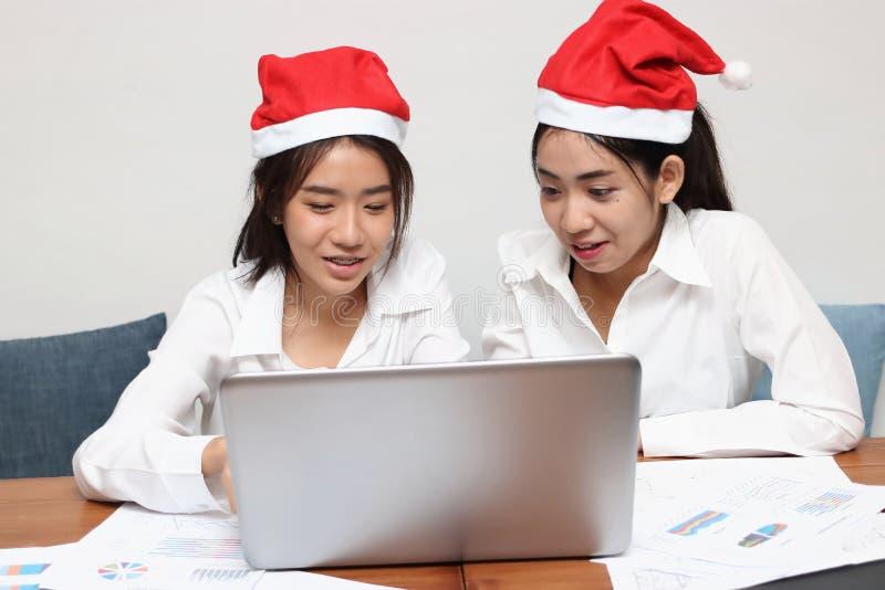 Zwei nette asiatische Geschäftsleute mit Weihnachtsmann-Hut, der an Arbeitsplatz des Büros zusammenarbeitet lizenzfreies stockfoto