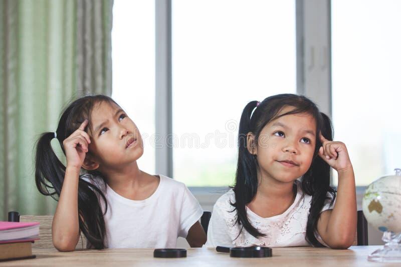 Zwei nette asiatische Kindermädchen, die wenn Hausarbeit im Raum denken, getan wird lizenzfreie stockbilder