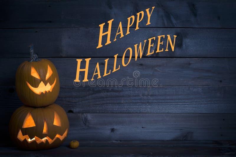 Zwei nette beleuchtete Kürbise mit glücklichem Halloween geschrieben auf einen dunkelblauen rustikalen hölzernen Brett-Hintergrun lizenzfreie stockfotografie