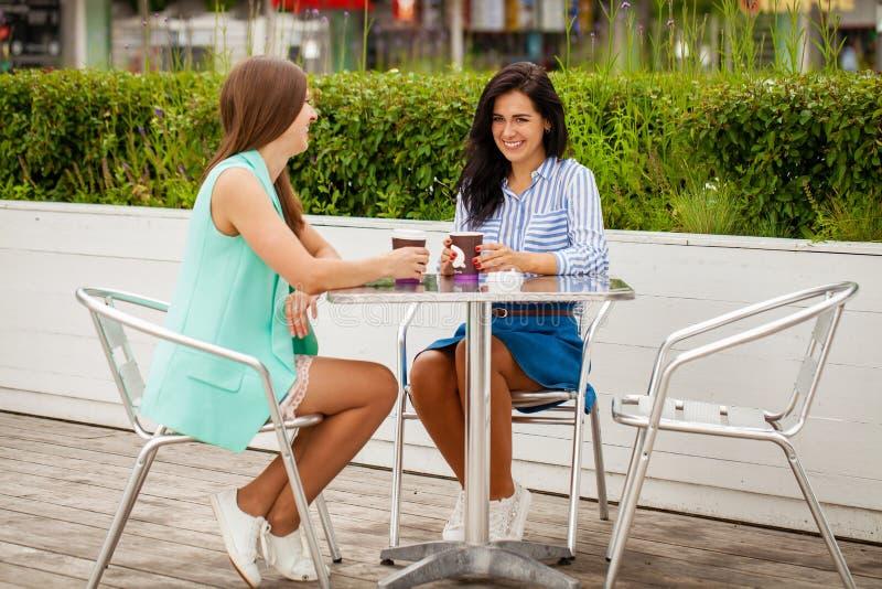 Zwei nette brunette Frauen, die Sommercafé stillstehen stockfotografie