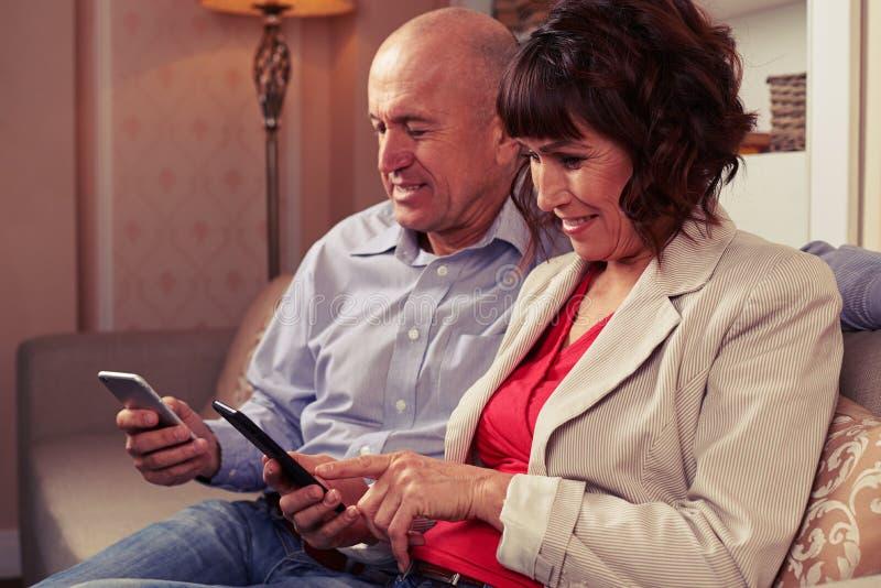 Zwei nette Einzelpersonen, die auf ihre Geräte klicken stockfoto