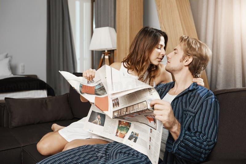 Zwei nette europäische Leute in der Liebe, küssend und umarmen beim auf Couch zu Hause sitzen und lesen Zeitung in den Pyjamas lizenzfreie stockfotos