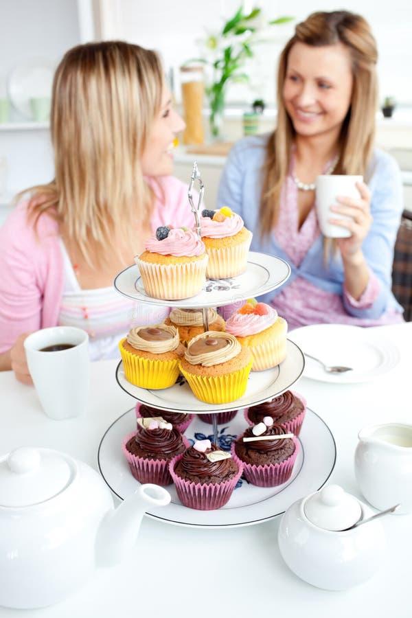 Zwei nette Freunde, die kleine Kuchen in der Küche essen lizenzfreies stockbild