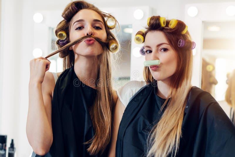 Zwei nette Freundinnen in den tragenden Lockenwicklern des schwarzen Kaps, die Schnurrbart aus ihrem Haar und Rolle im Frisörsalo stockfoto