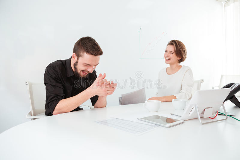 Zwei nette Geschäftsleute, die auf Sitzung sprechen und lachen stockfotografie