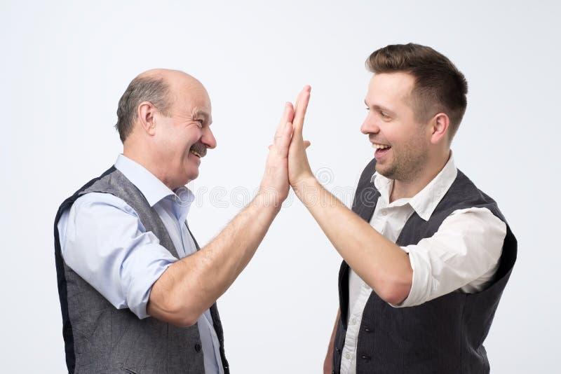 Zwei nette Geschäftsleute, die Hände und Lächeln sich klatschen lizenzfreie stockfotografie