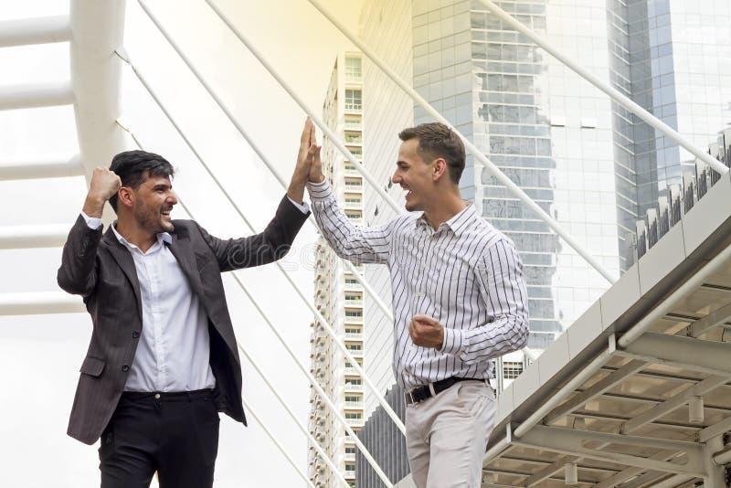 Zwei nette Geschäftsleute, die Hände und Lächeln sich klatschen stockbilder