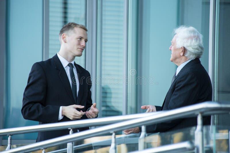 Zwei nette Geschäftsmänner, die über Geschäft während einer von ihnen Computermonitor zeigend sprechen lizenzfreies stockbild