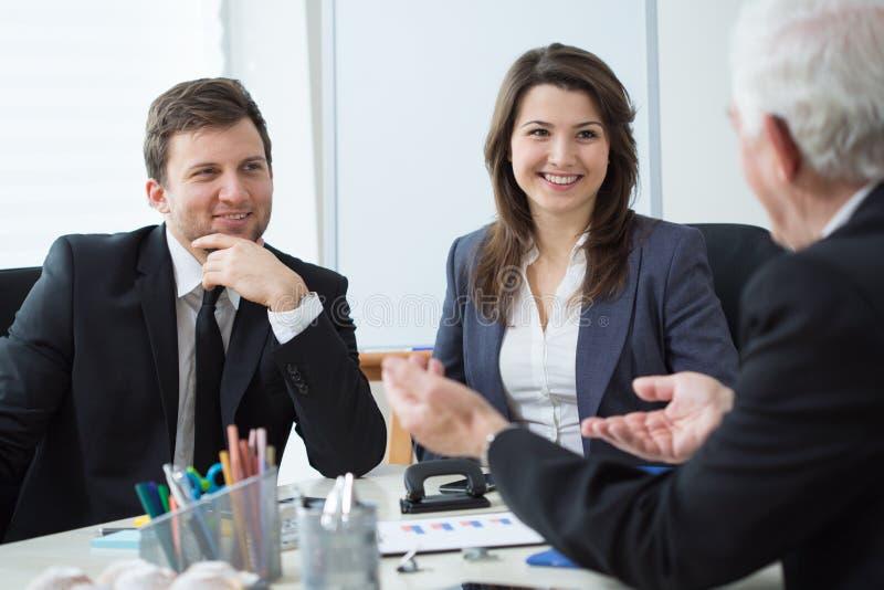 Zwei nette Geschäftsmänner, die über Geschäft während einer von ihnen Computermonitor zeigend sprechen stockfoto