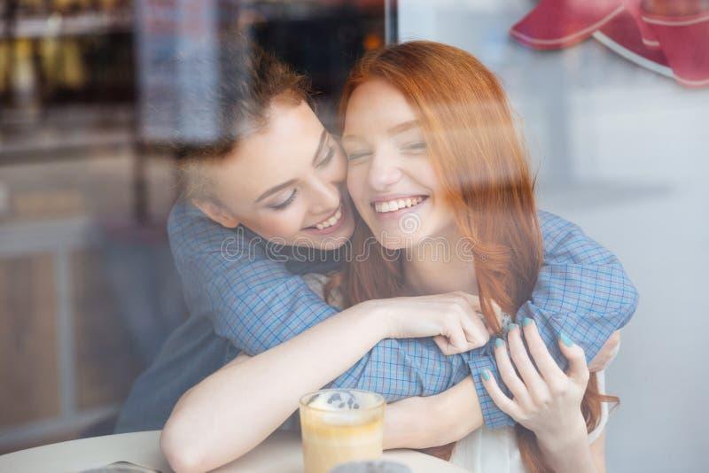 Zwei nette glückliche Frauen, die im Café umarmen stockfotos