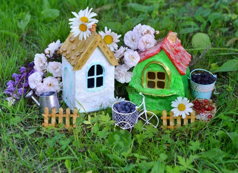 Zwei nette Häuser mit Sommerbeere, -Gießkanne und -blumen im Garten stockfoto