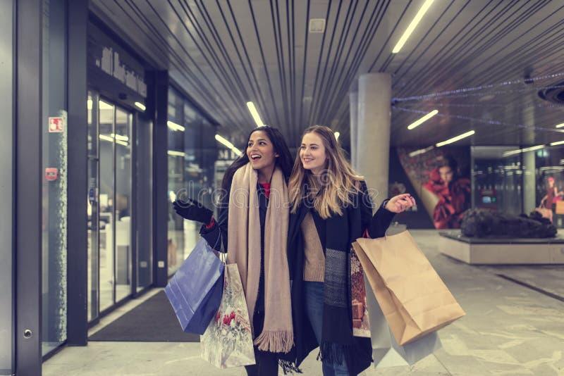 Zwei nette jugendliche junge Frauen, die an einem kalten Winterabend, beim Halten von großen Einkaufstaschen kaufen stockbild