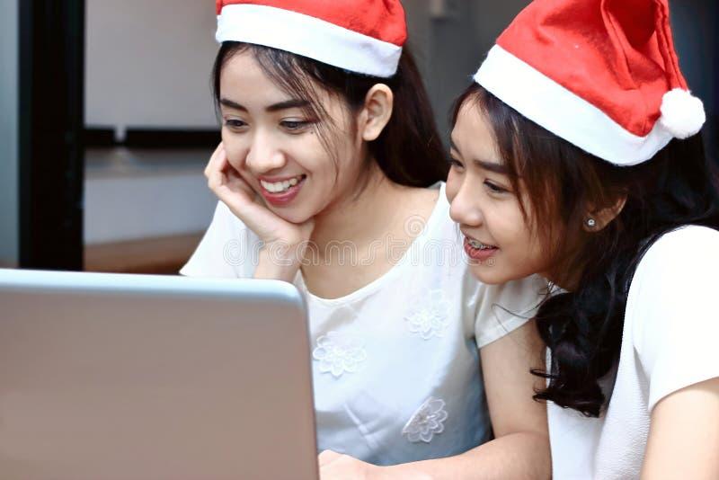 Zwei nette junge asiatische Geschäftsfrauen mit Weihnachtsmann-Hut online zusammen kaufend im Weihnachtsfeiertag Internet der Sac lizenzfreie stockfotografie