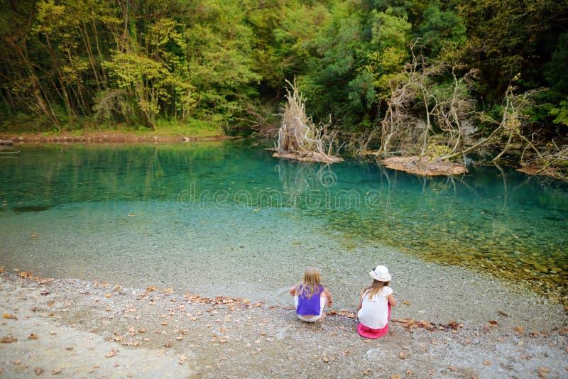 Zwei nette junge Schwestern, die Spaß durch Voidomatis-Fluss am warmen und sonnigen Sommertag während der Familienurlaube in Zago stockbilder