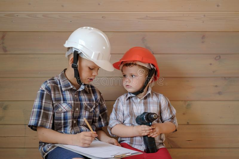 Zwei nette Jungen in den Bausturzhelmen besprechen einen Plan für die bevorstehende Arbeit Kinder spielen Erbauer stockfoto