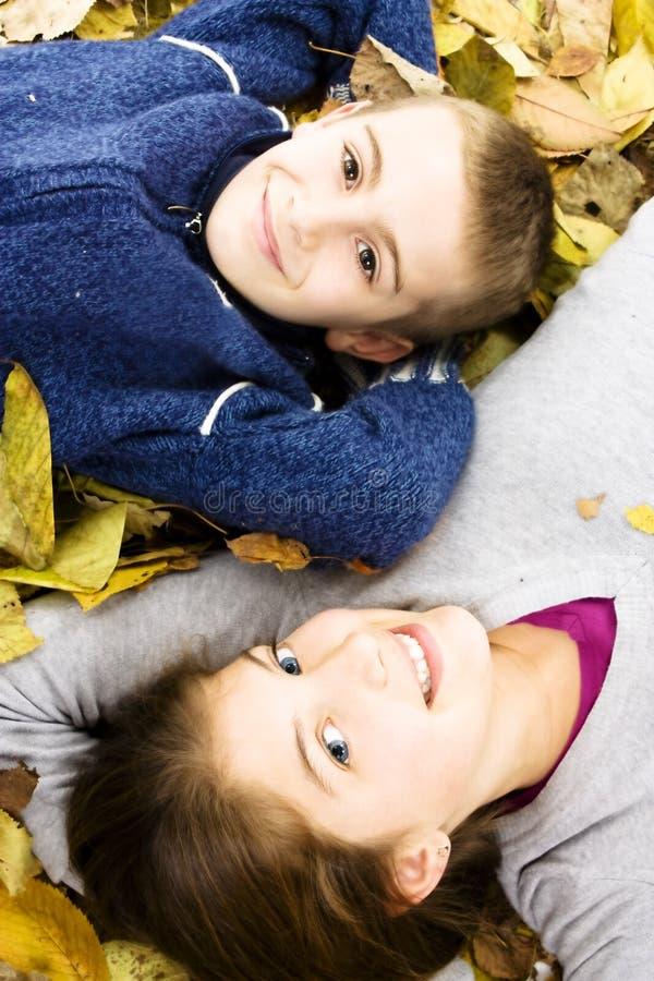 Zwei nette Kinder, die sich mit Blättern herum hinlegen stockfoto