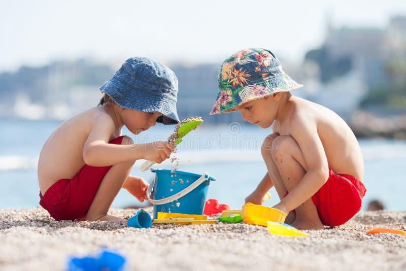 Zwei nette Kinder, spielend im Sand auf dem Strand lizenzfreies stockfoto