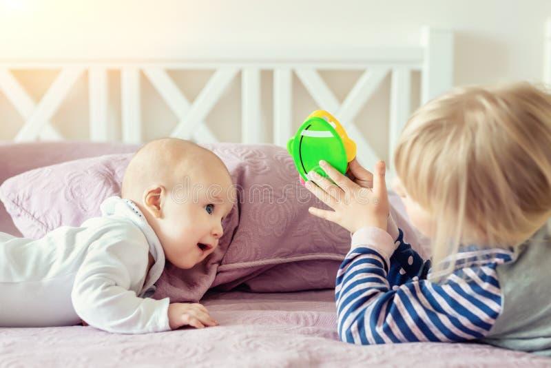 Zwei nette kleine Geschwister, die zusammen auf Bett spielen Schwester und Bruder, die Spaß am Schlafzimmer im Morgen haben Glück lizenzfreie stockfotos