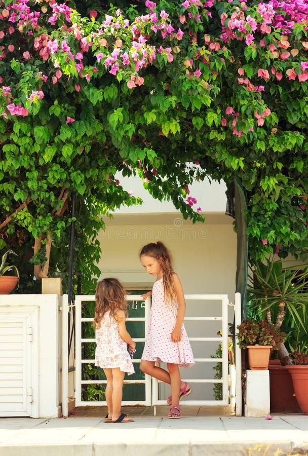 Zwei nette kleine Mädchen, die nahe dem Haus sprechen lizenzfreie stockfotografie