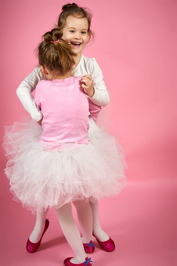 Zwei nette kleine Mädchen in Tulle-Röcken auf einem rosa Hintergrund lizenzfreie stockfotos