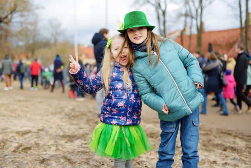 Zwei nette Mädchen, die grüne Hüte und das Zubehör feiert St- Patrick` s Tag in Vilnius tragen stockbilder