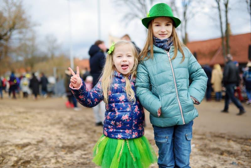 Zwei nette Mädchen, die grüne Hüte und das Zubehör feiert St- Patrick` s Tag in Vilnius tragen lizenzfreie stockfotos