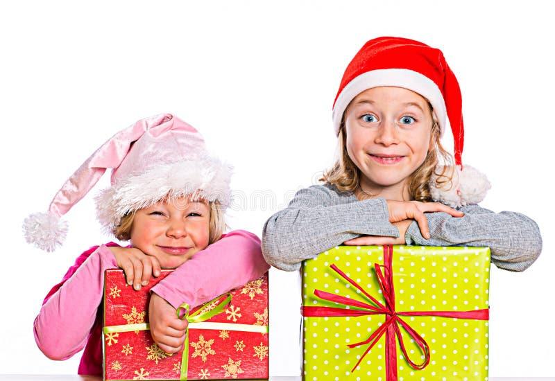 Zwei nette Mädchen mit Weihnachtsgeschenk lizenzfreie stockfotos